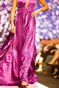 Modelka na wybiegu w długiej rozkloszowanej sukni z satyny jedwabnej koloru fuksji