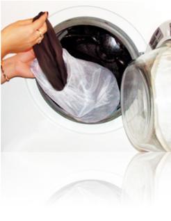 Kobieca dłoń wyciągająca rajstopy ze średniego woreczka do prania w kolorze białym na brzegu wejścia do pralki