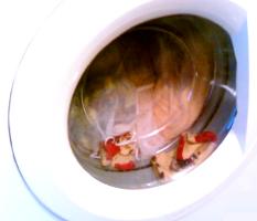 Małe skarpetki wciśnięte pod szybę pralki i reszta  prania w workach