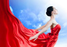 Piękna młoda kobieta o arystokratycznej urodzie w królewskiej sukni z  czerwonej jedwabnej satyny. Wydaje się jakby suknia dała jej możliwość  wzniesienia się ponad wszystko